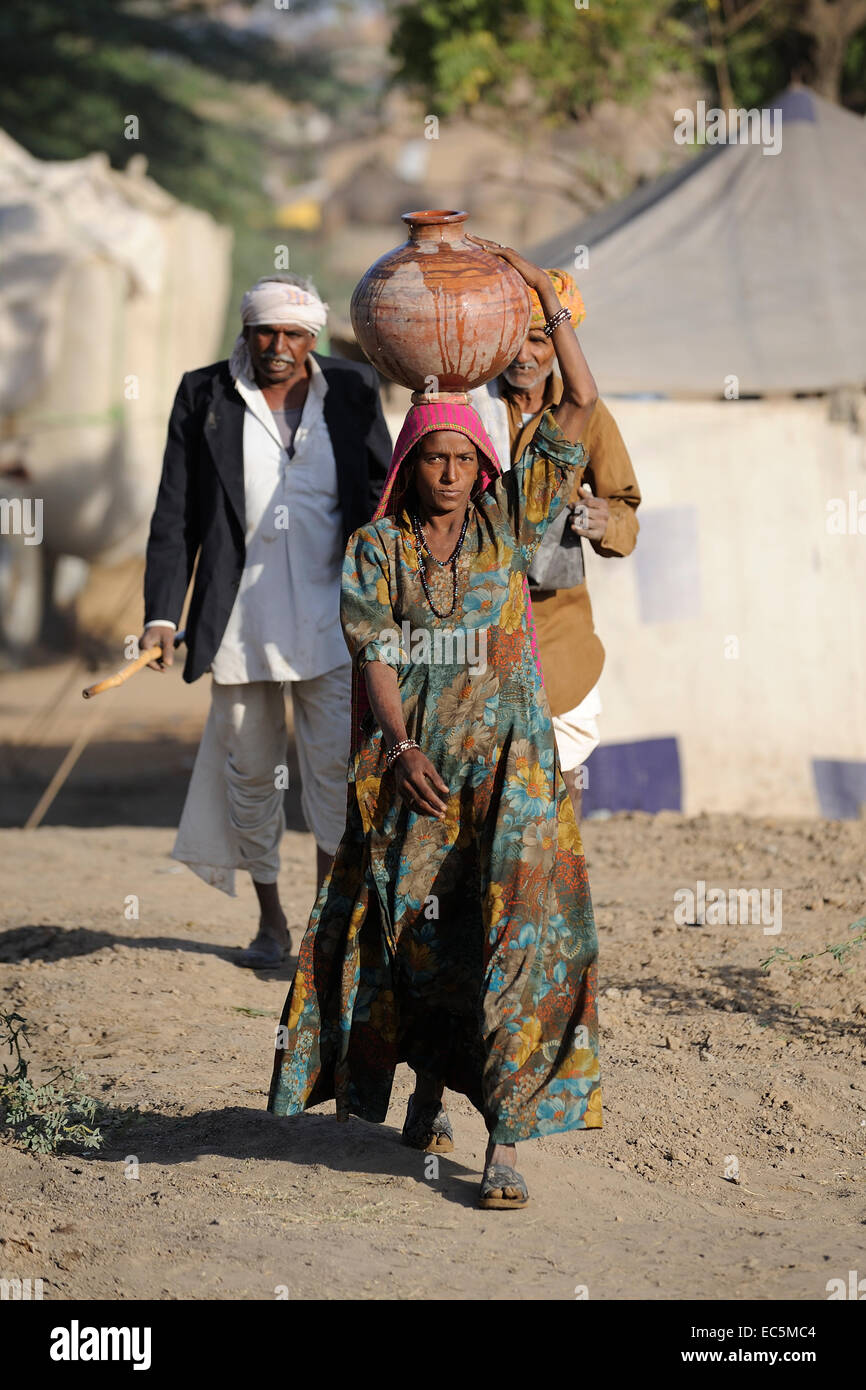 Indian woman carry a water pot on her head - Stock Image