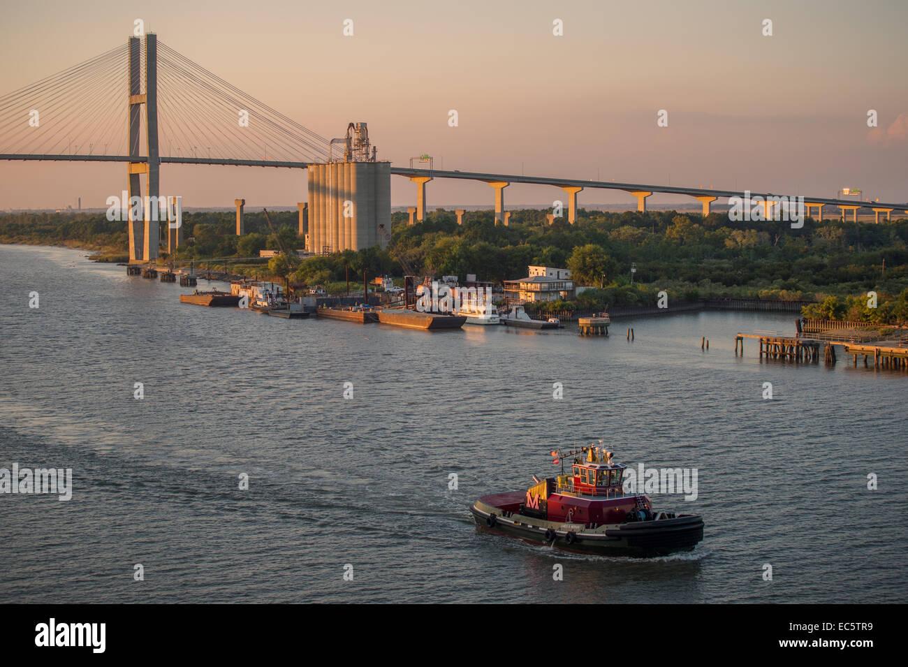 Pilot boat at dusk on Savannah River with Eugene Talmadge Memorial Bridge in the background. - Stock Image