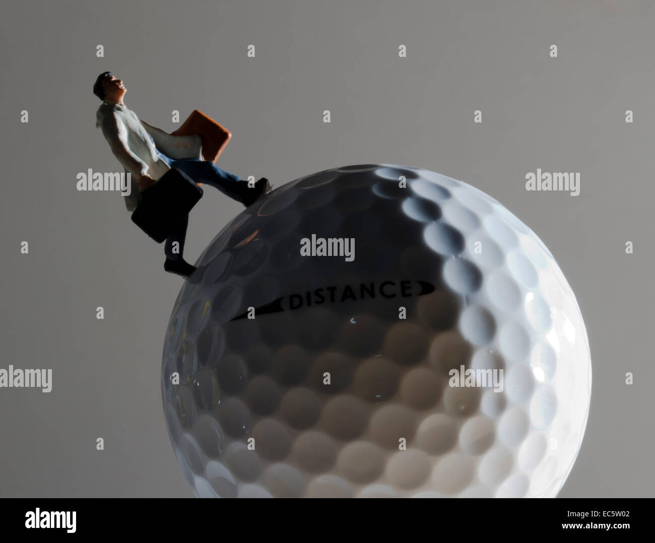 Man with lugage walking on golfball - Stock Image
