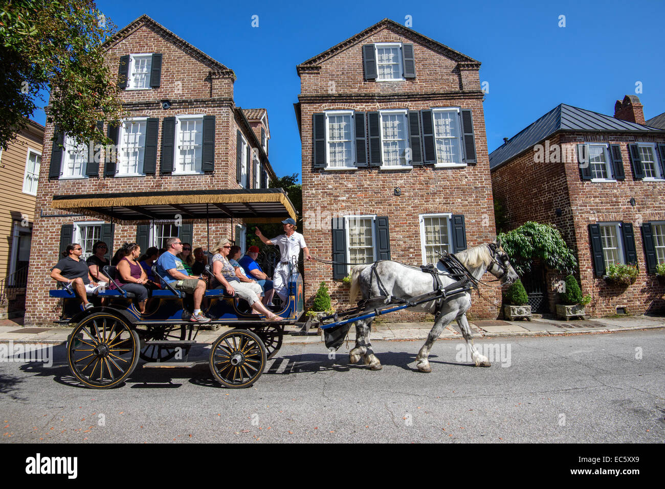 Horse carriage with tourists enjoying historic traditional residential architecture on King Street in Charleston, - Stock Image