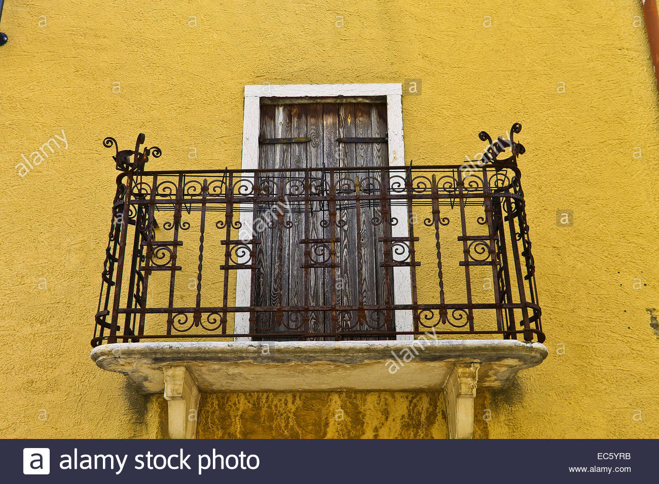 Wrought iron rails, old balcony, yellow walls San Georgio Stock ...