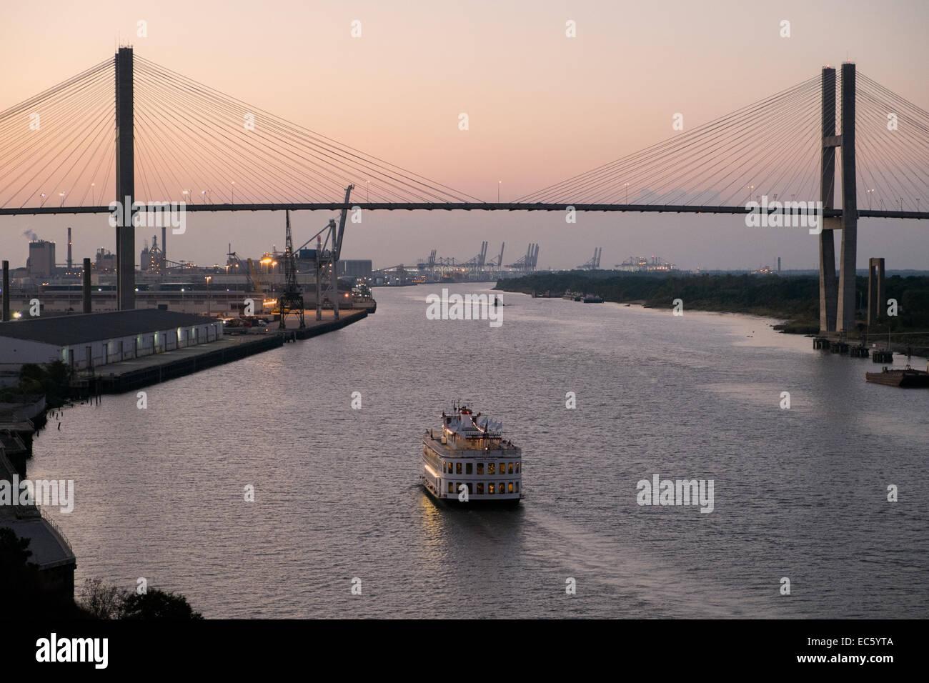 Riverboat cruising at dusk on Savannah River below the Eugene Talmadge Memorial Bridge. - Stock Image