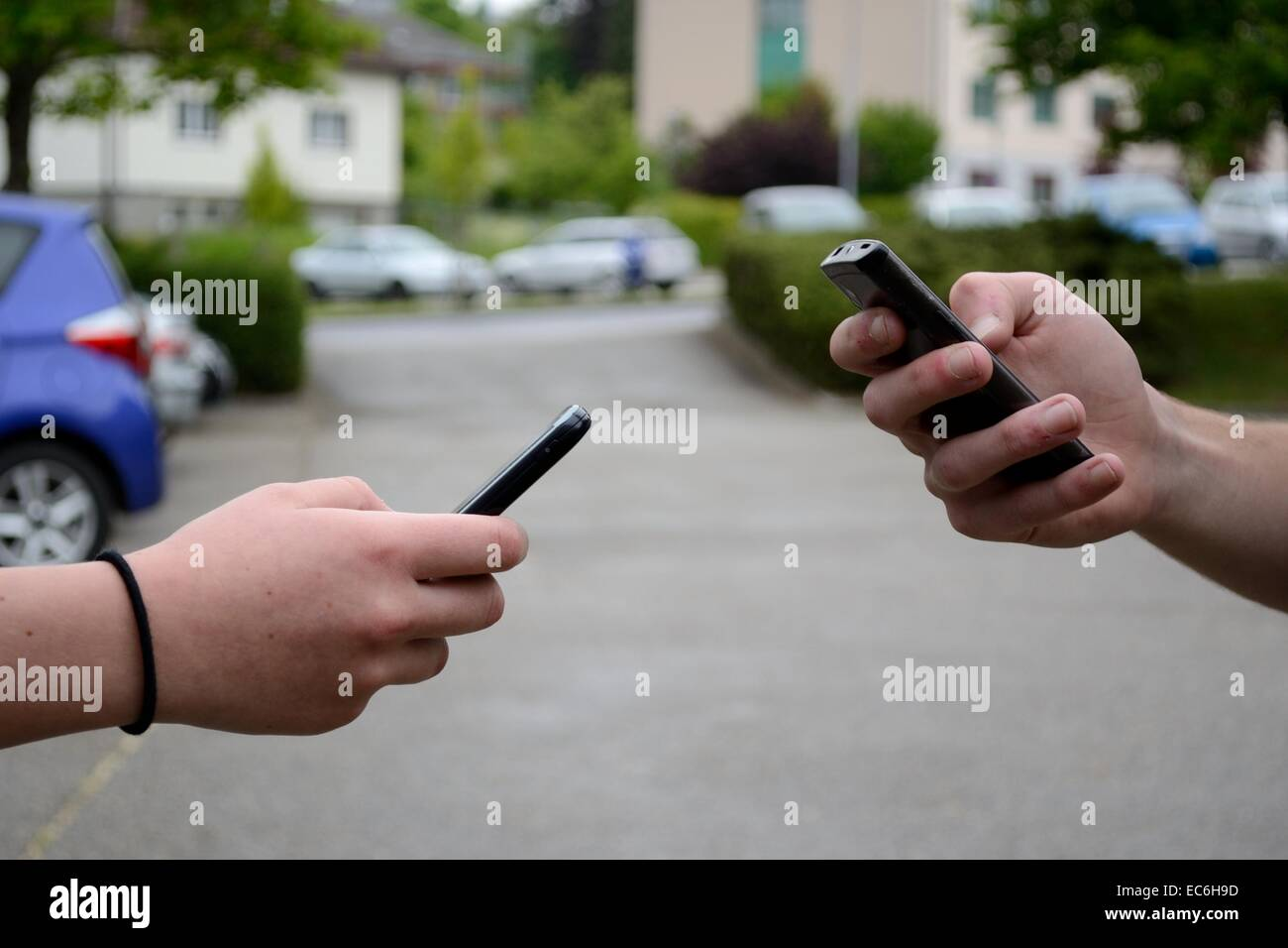 Two people communicate with the mobile phone - Stock Image