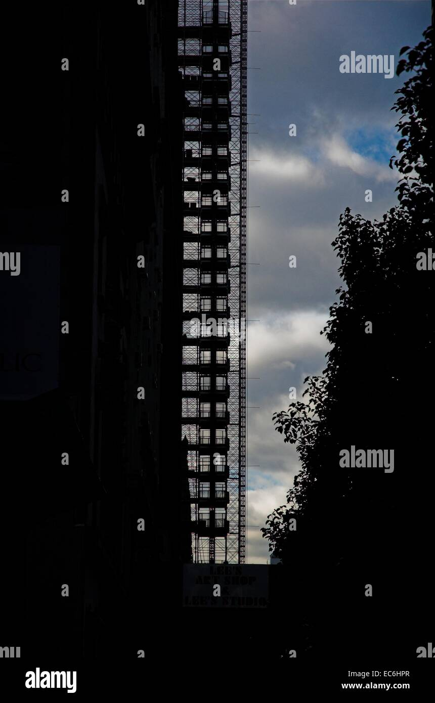 Silhouetted scaffolding against a building on a NY city street - Stock Image
