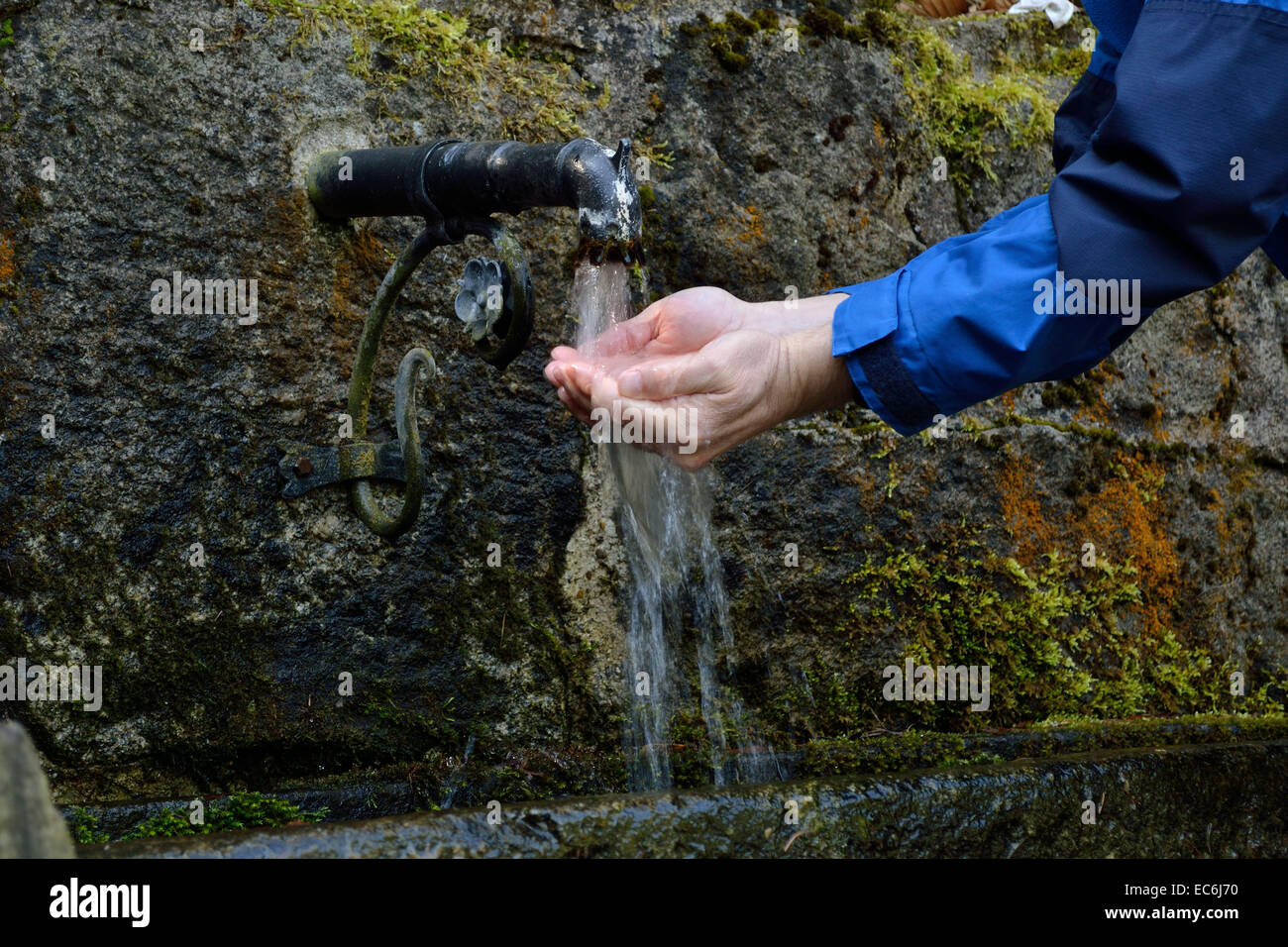 Person refreshes itself at a water source - Stock Image