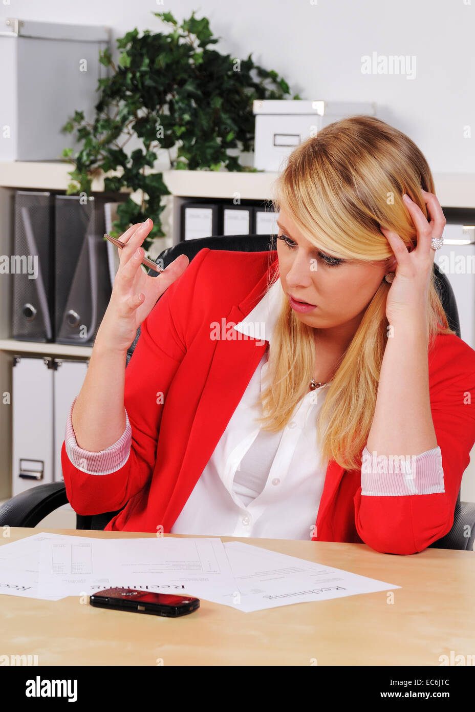 young woman in a office sitting hopeless above outstanding bills - Stock Image