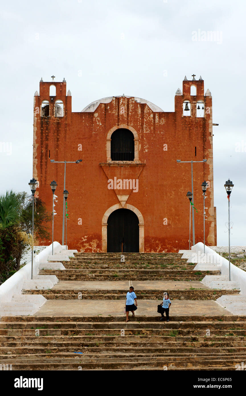 Two Mexican school children in front of the Spanish colonial church in Santa Elena, Yucatan, Mexico - Stock Image