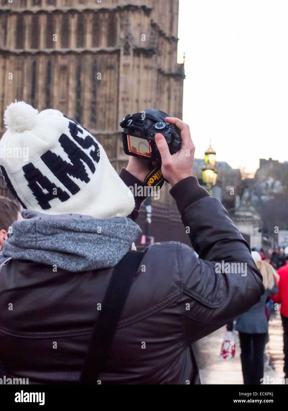 A photographer checks his images on the back of his camera in the street - Stock Image