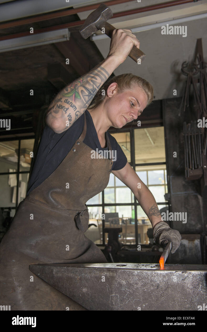 Female Blacksmith Working At Ambos With Hammer On Redhot