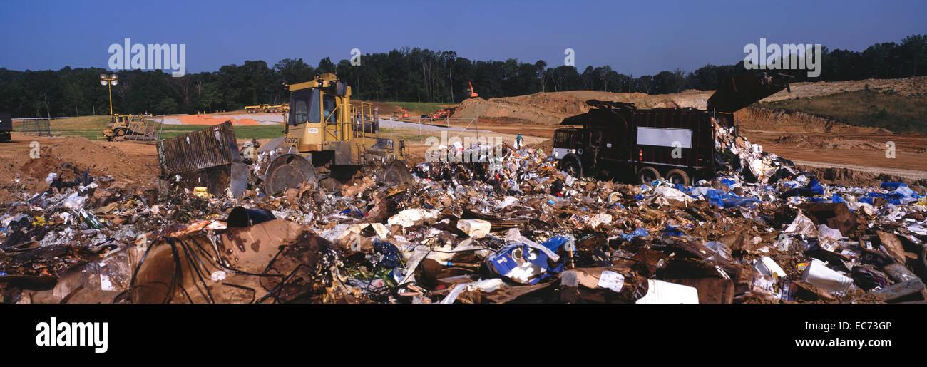 Heavy machinery moves refuse at sanitary landfill. - Stock Image