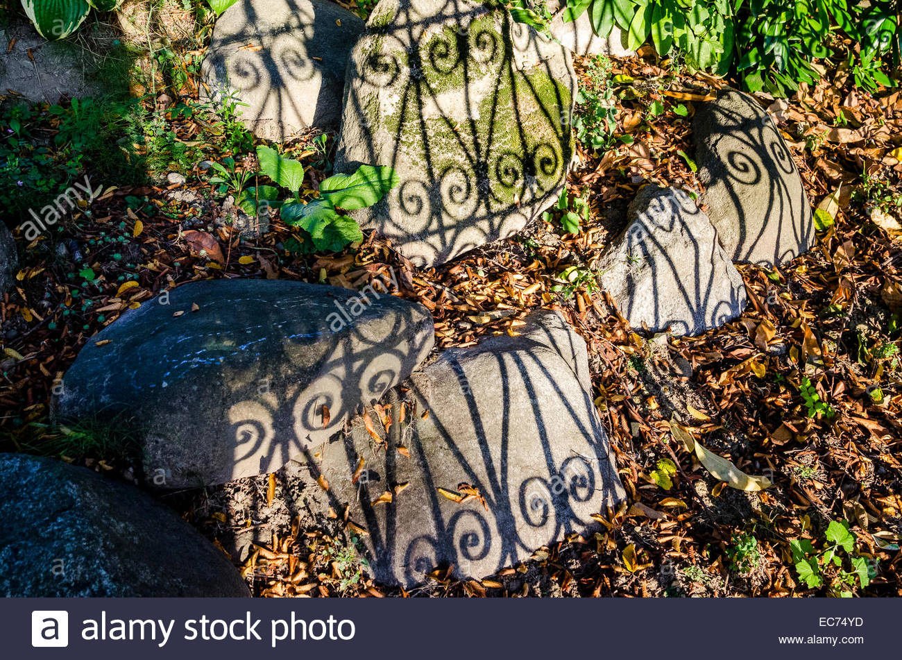 Shadow of wrought iron fence - Stock Image