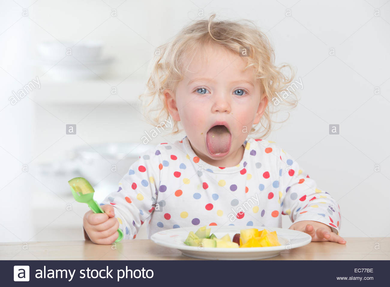 Baby eating fruit making a face - Stock Image