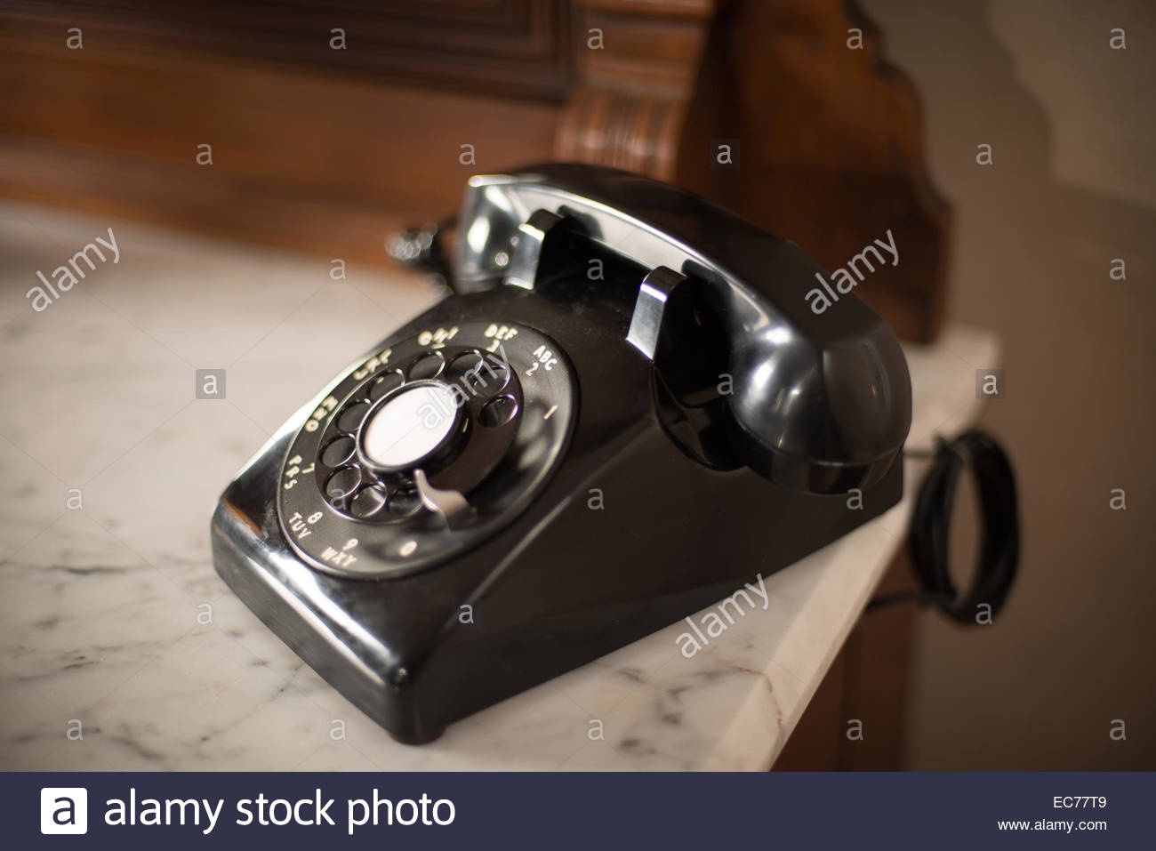 old style dial telephone sitting on a marble counter - Stock Image