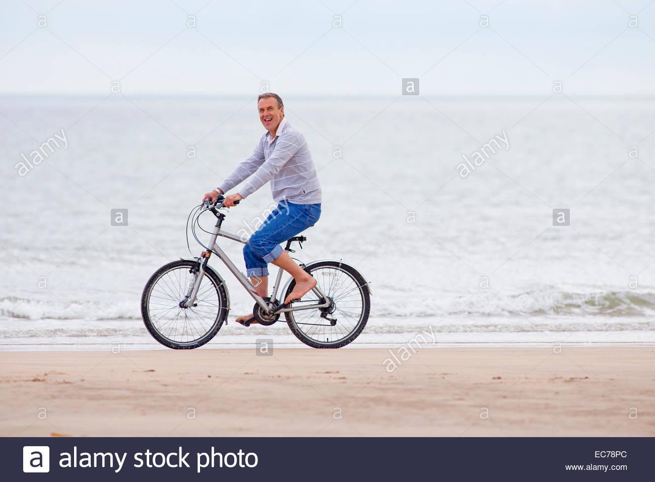 Older man riding bicycle on beach - Stock Image