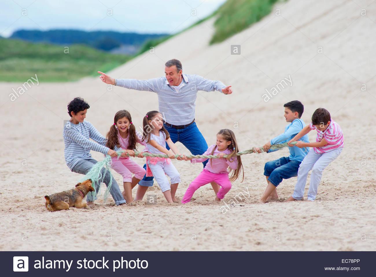 Grandfather supervising grandchildren playing tug-of-war on beach - Stock Image