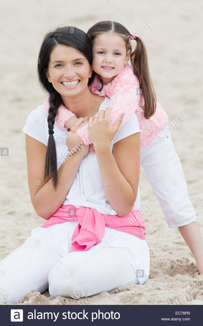 Mother and daughter hugging on beach - Stock Image