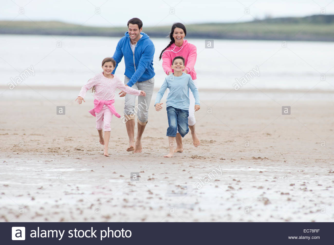 Parents chasing children on beach - Stock Image