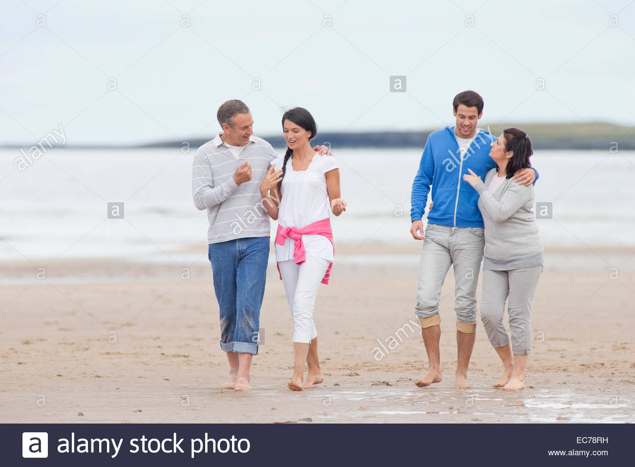 Parents and adult offspring walking together on beach - Stock Image