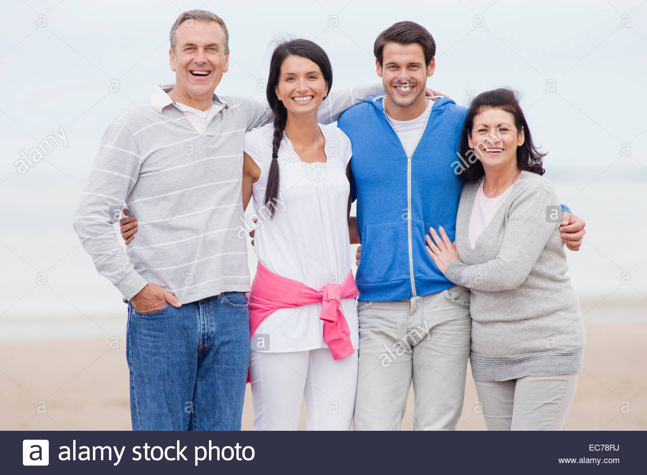 Parents and adult offspring smiling together on beach - Stock Image