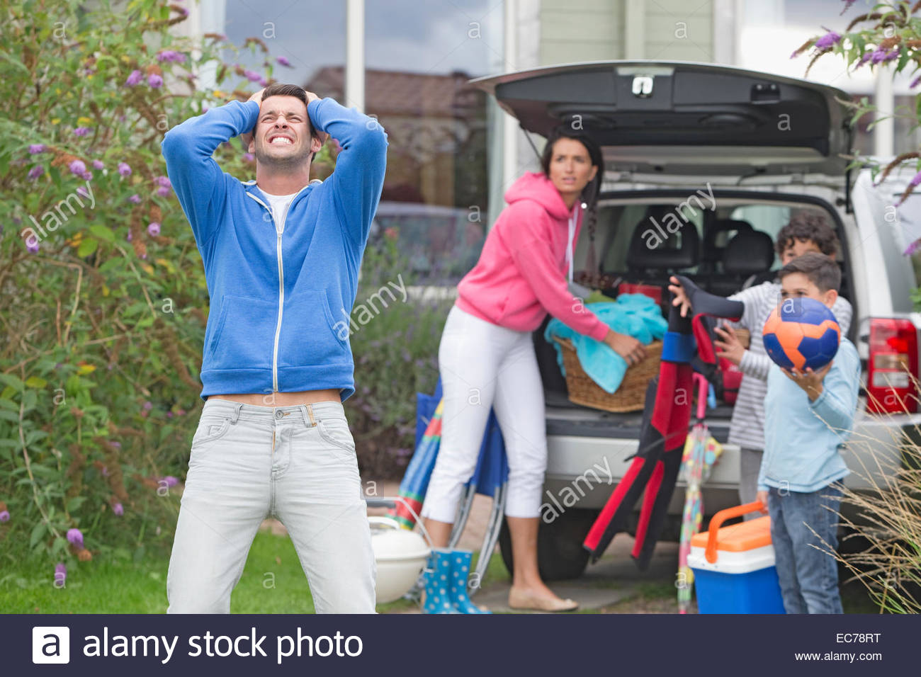 Frustrated father shouting as family packs car for vacation - Stock Image