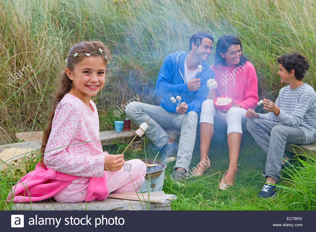 Family roasting marshmallows at campsite - Stock Image