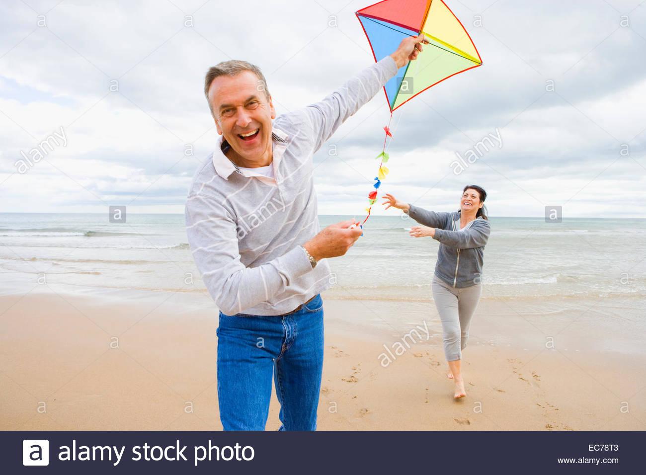 Older couple flying kite on beach - Stock Image