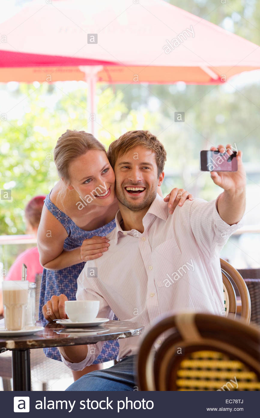 Couple taking selfie in outdoor cafe Stock Photo