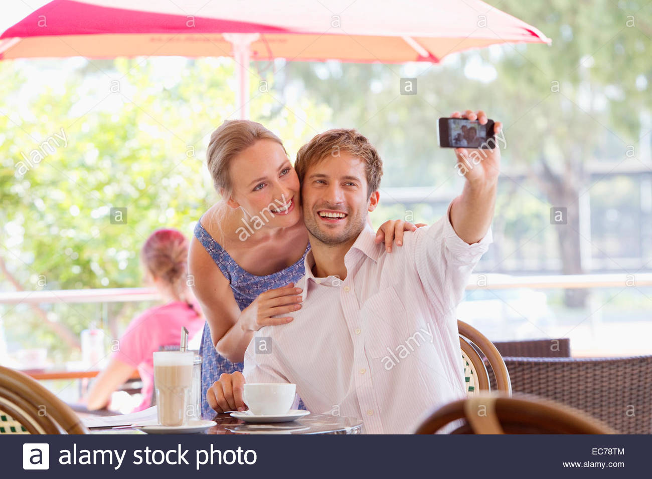 Couple taking selfie in outdoor cafe - Stock Image