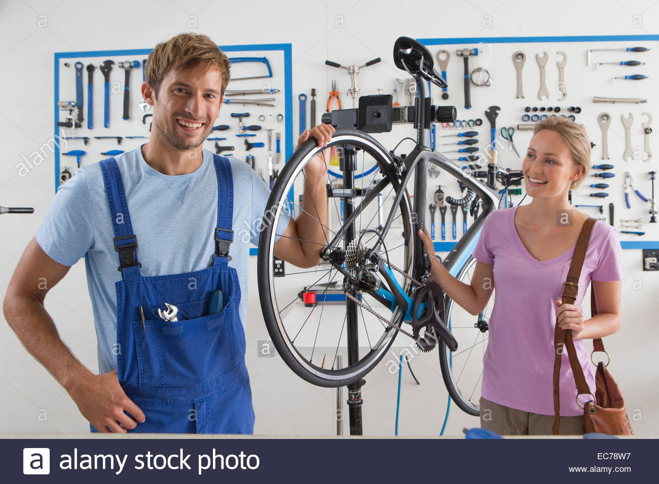 Cycle technician repairing female customers bicycle - Stock Image