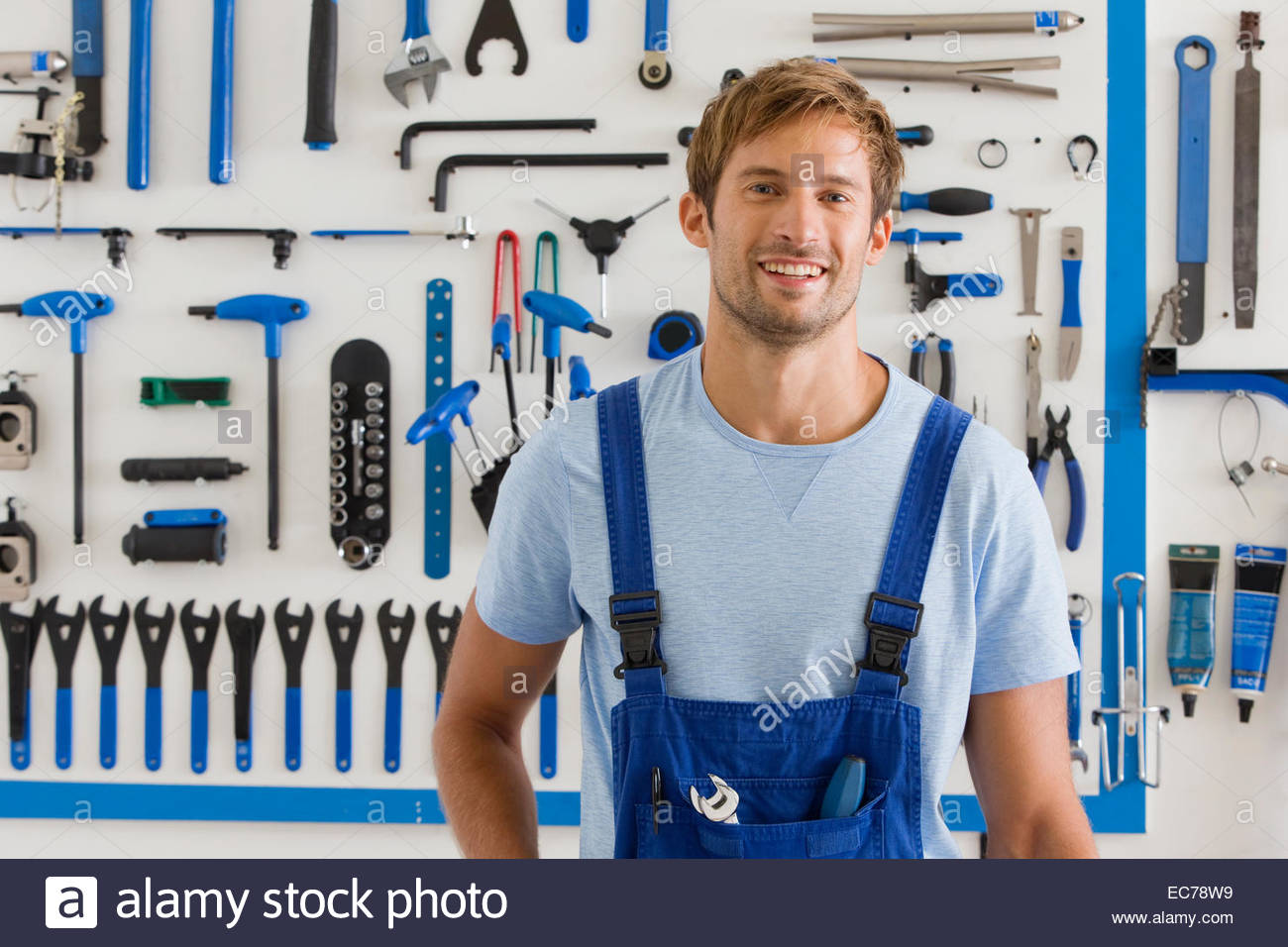 Cycle technician in workshop smiling at camera - Stock Image