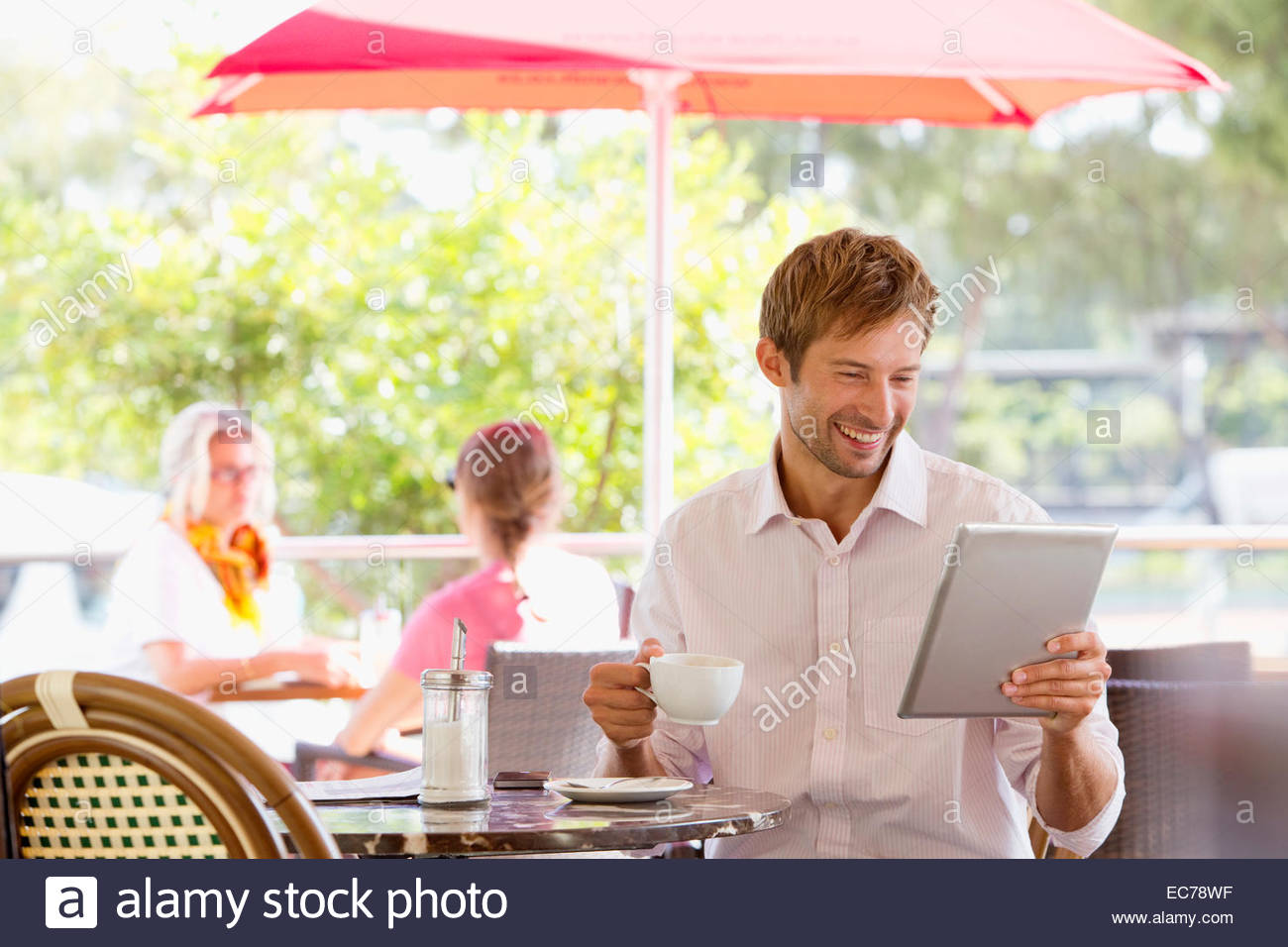Man drinking coffee looking at digital tablet in outdoor caf - Stock Image