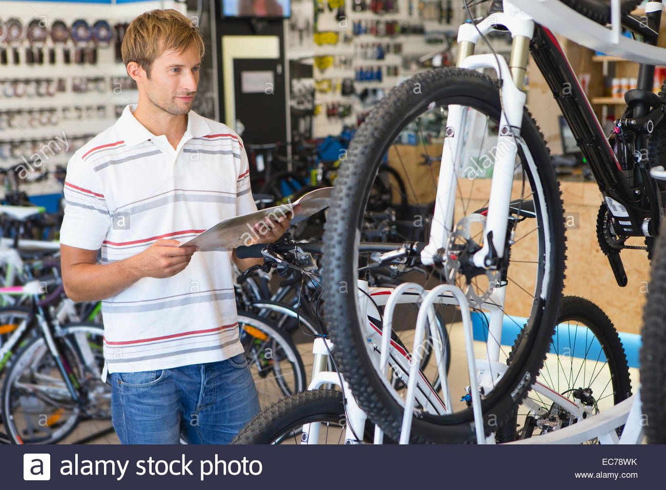 Man choosing a bicycle in shop - Stock Image