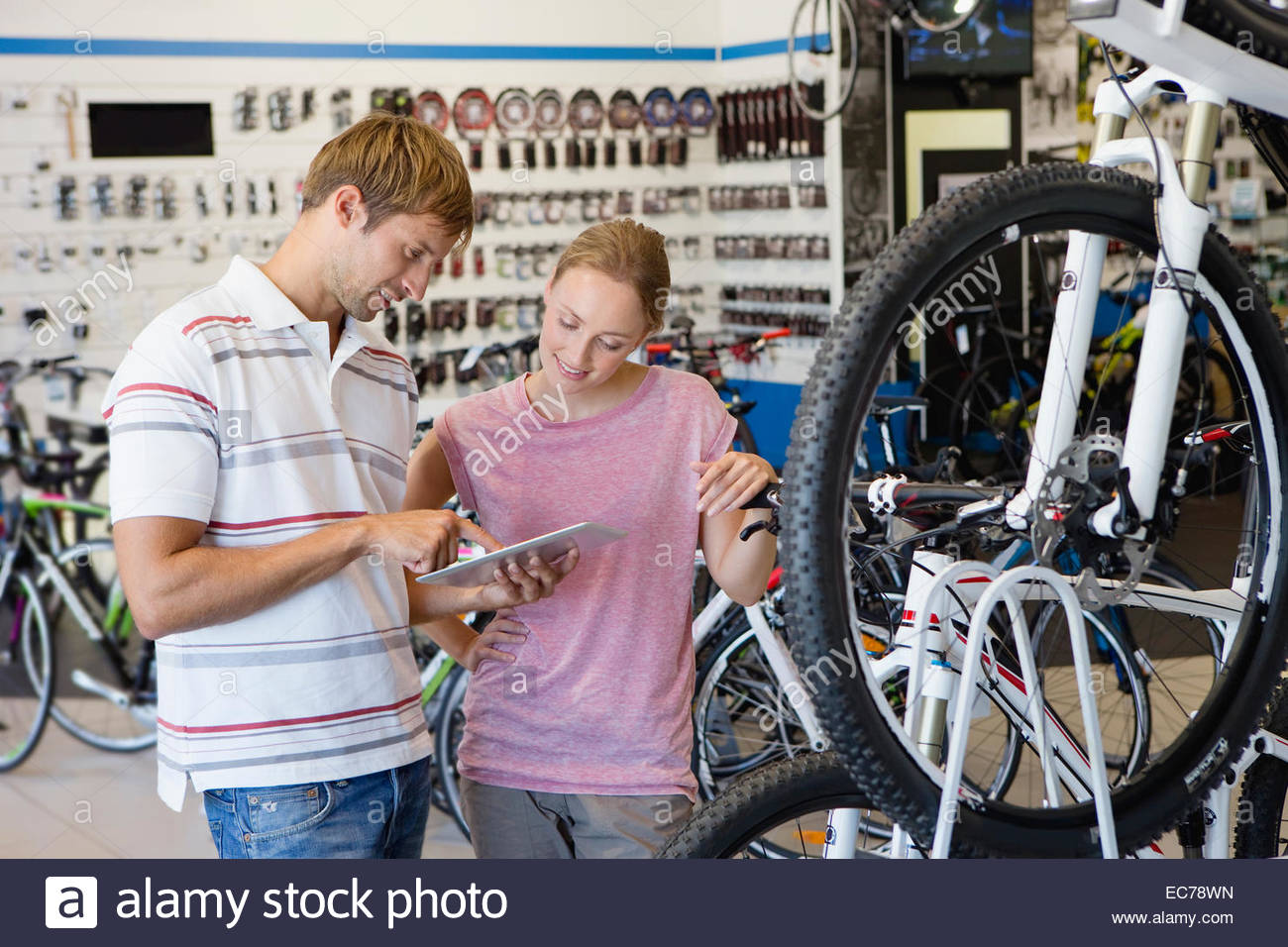 Store manager assisting customer in bicycle shop - Stock Image