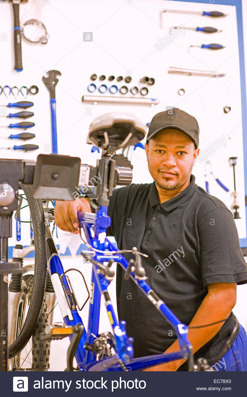 Cycle technician repairing bicycle - Stock Image