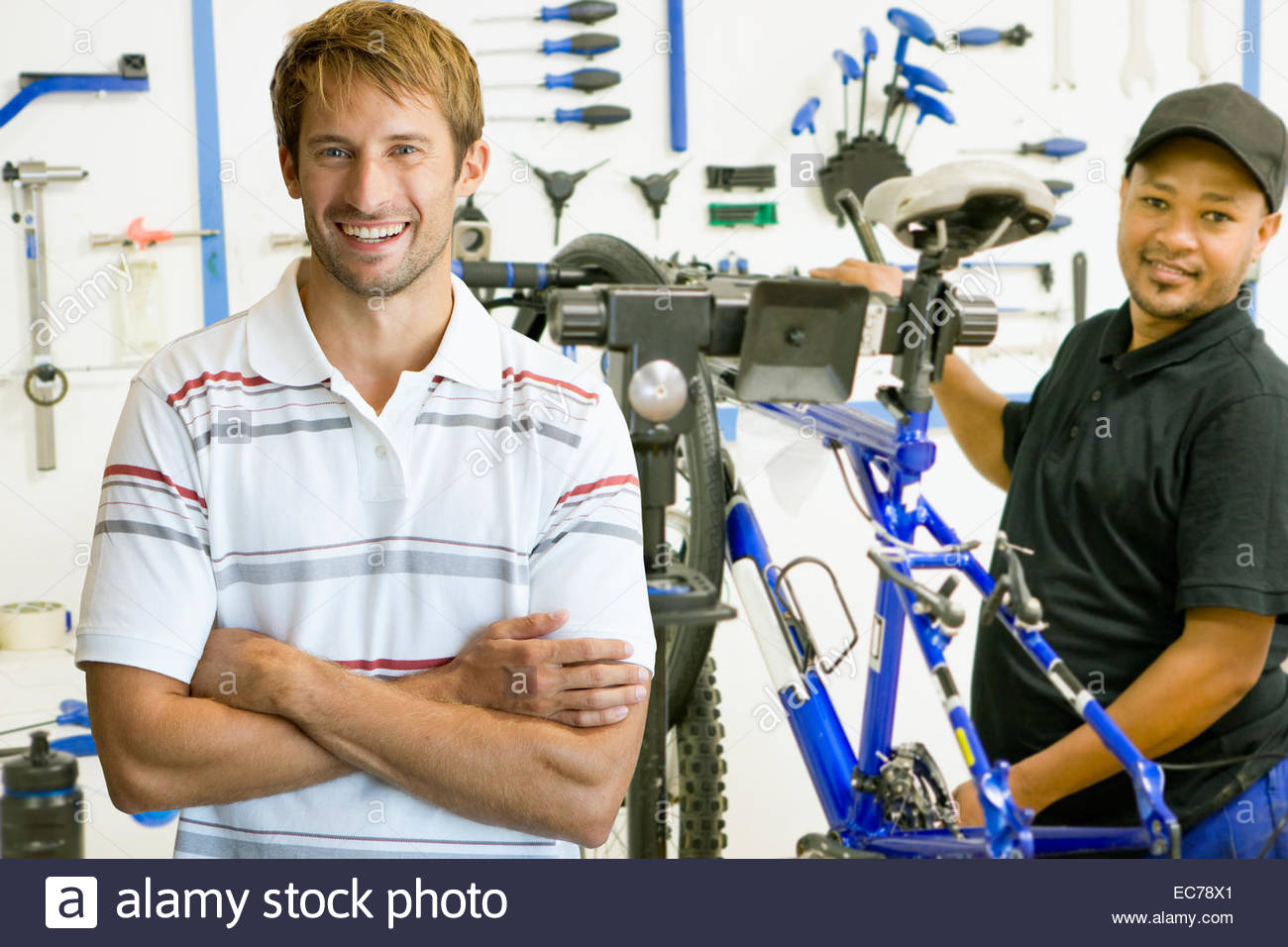 Portrait of store manager and cycle technician in workshop - Stock Image