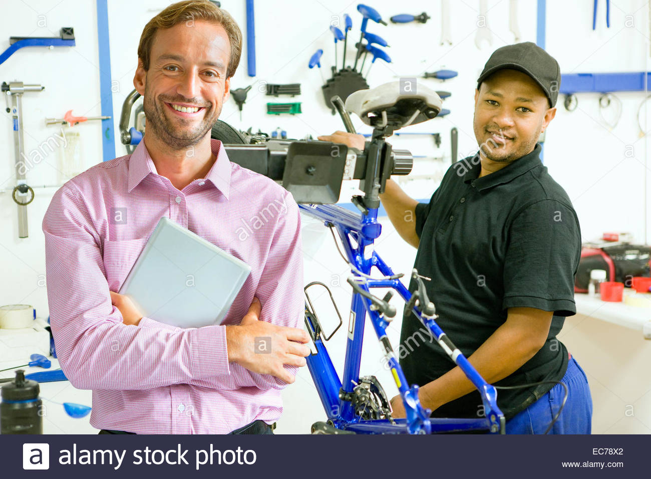 Portrait of store owner and cycle technician in workshop - Stock Image