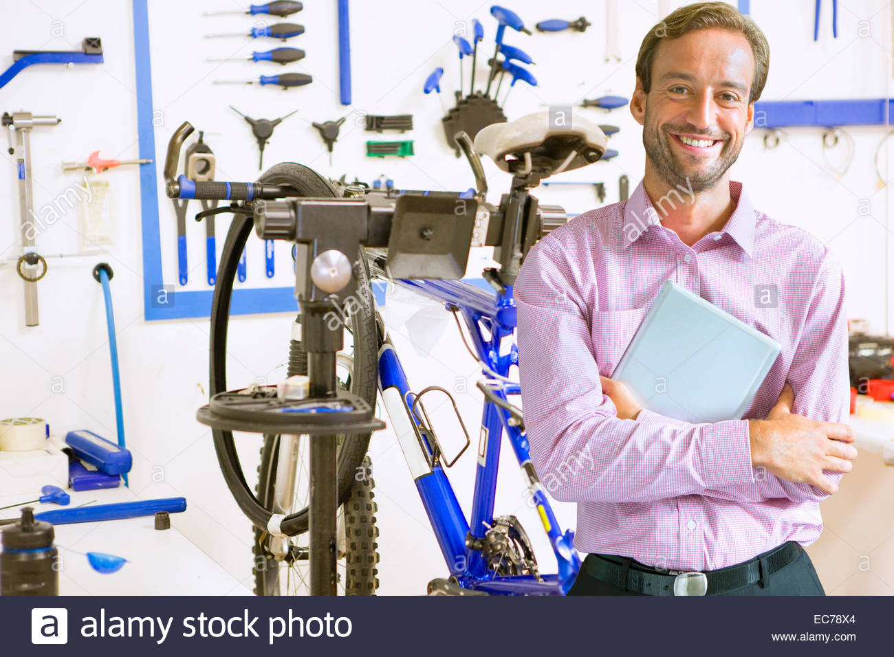 Shop owner in bicycle workshop - Stock Image
