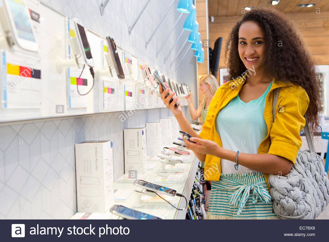 Young woman browsing in phone store - Stock Image
