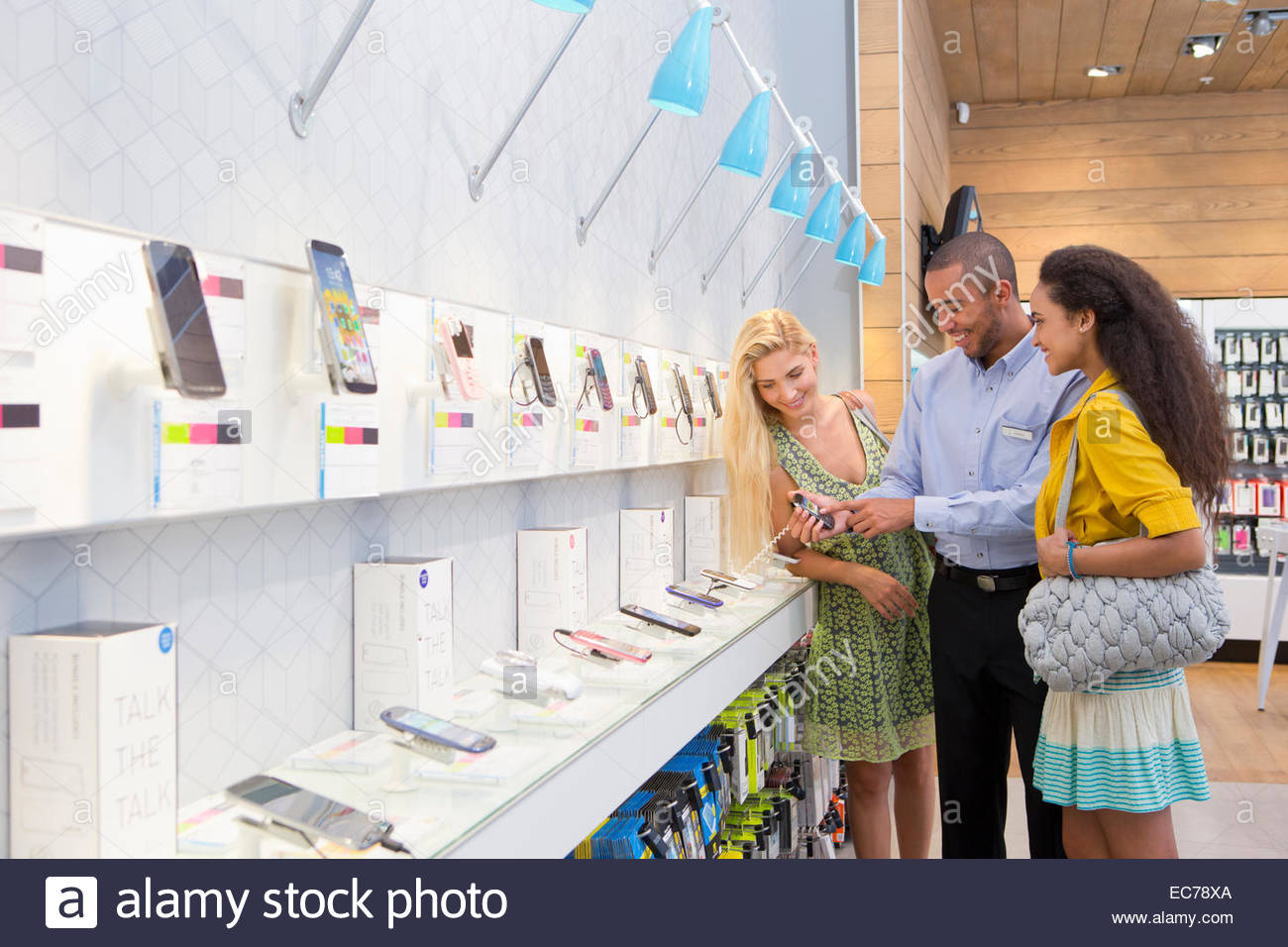 Store manager assisting two female customers in phone store - Stock Image