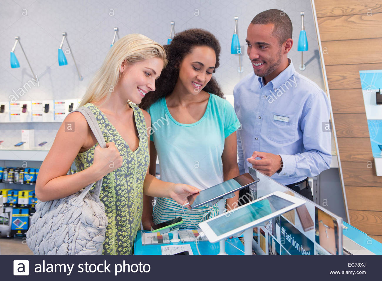 Store manager assisting two female customers in computer store - Stock Image