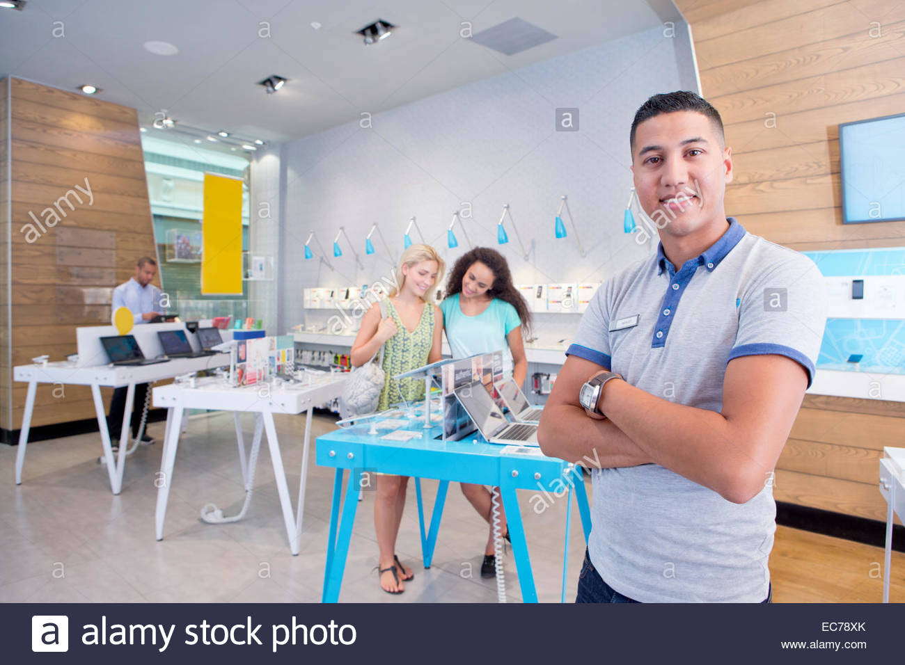 Store assistant in computer store with customers - Stock Image