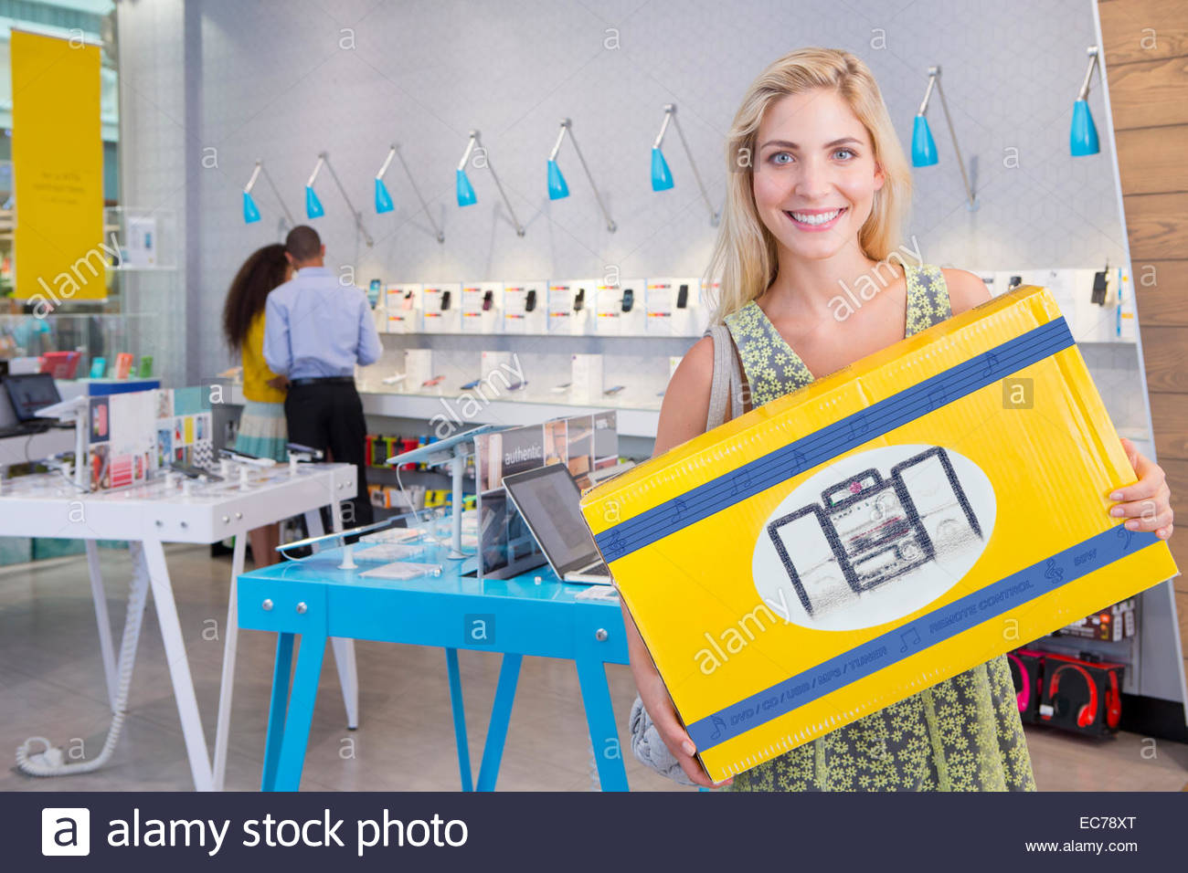 Woman with purchase in electrical store - Stock Image