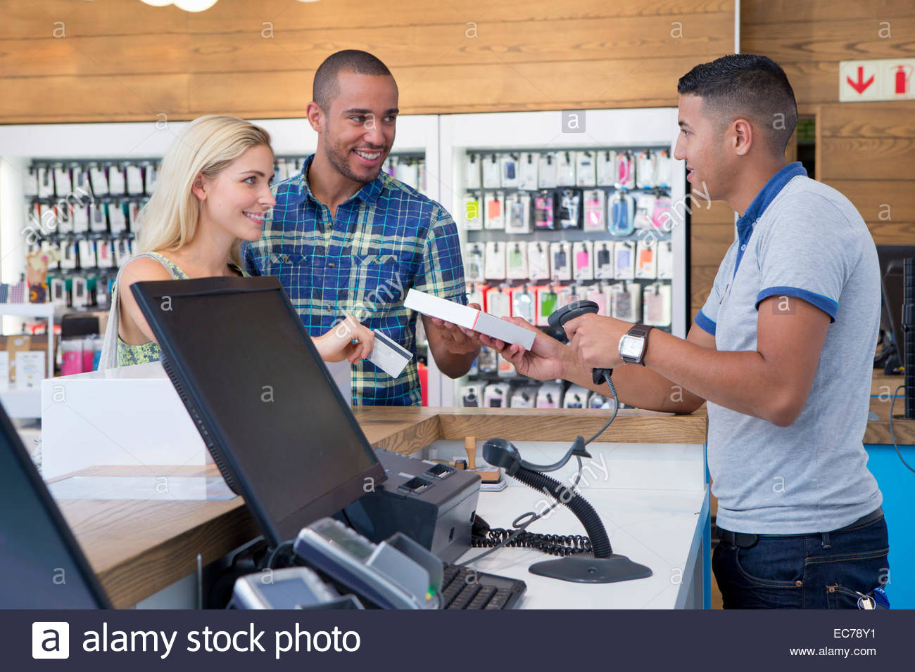 Couple making a purchase from store assistant in shop - Stock Image