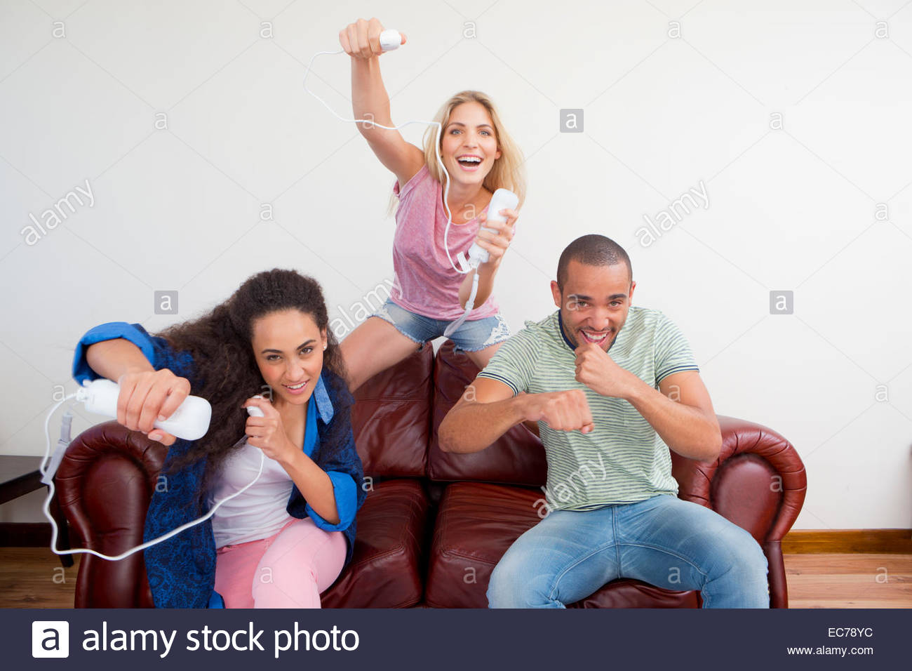 Three friends playing video game on sofa - Stock Image