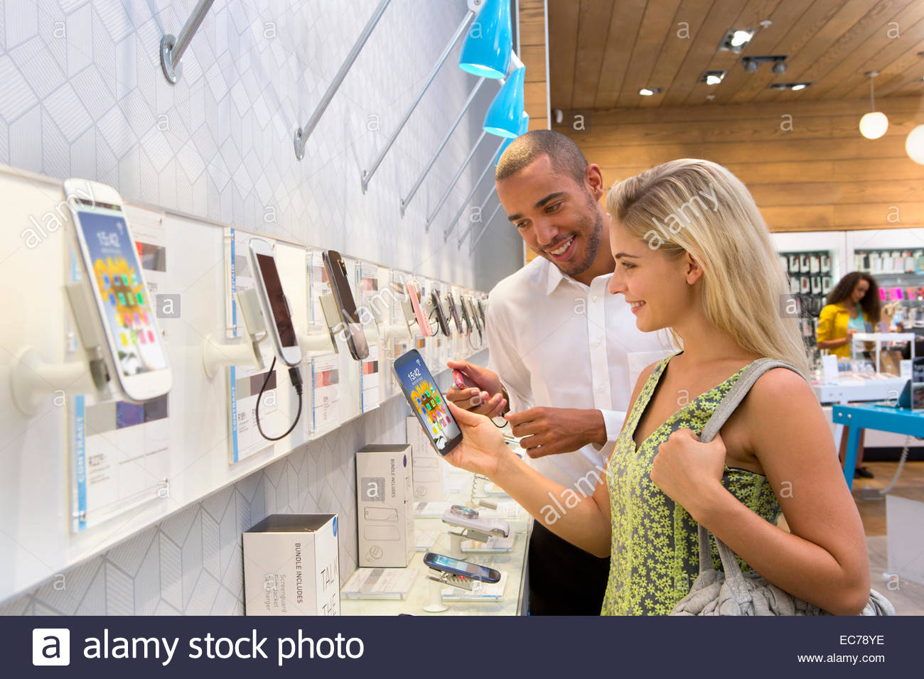 Store manager assisting customer in phone store - Stock Image