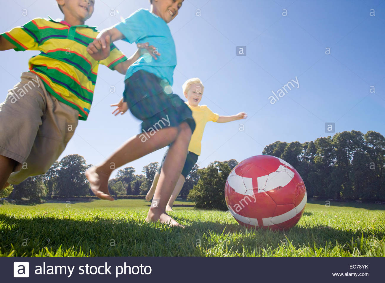 Smiling boys playing soccer in park Stock Photo