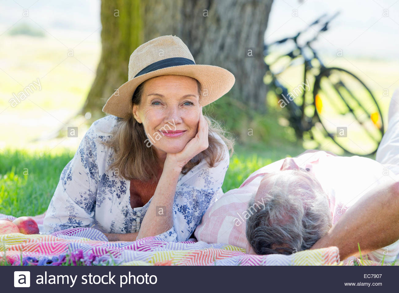 Senior Couple lying on picnic blanket in field - Stock Image