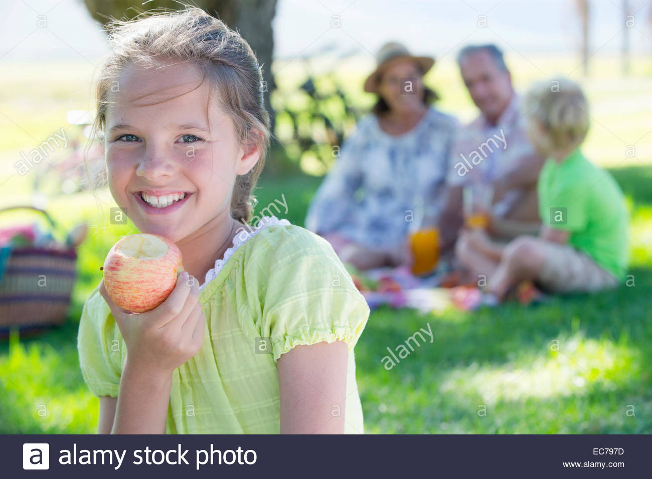 Portrait of girl eating apple with picnicking family in background - Stock Image