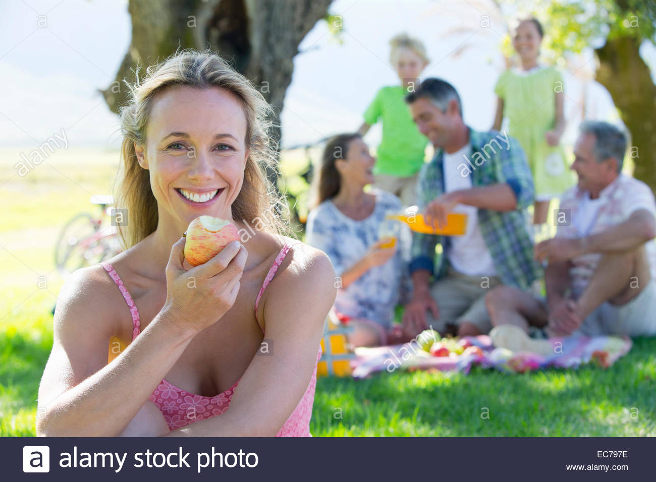 Woman eating apple with Multi generation family having a picnic in countryside - Stock Image