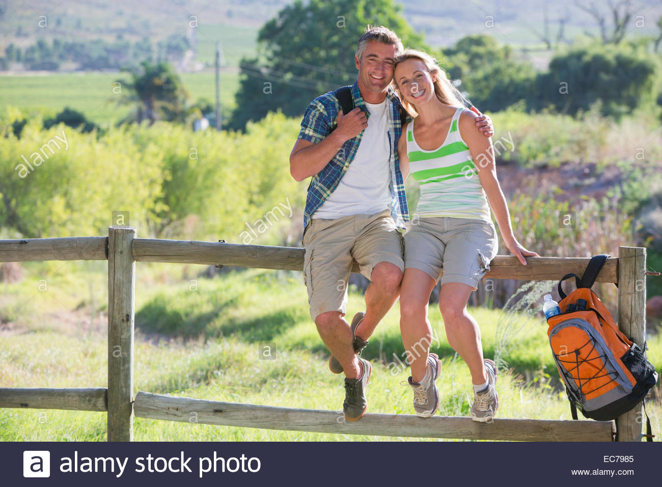 Couple resting on a fence in a rural setting - Stock Image